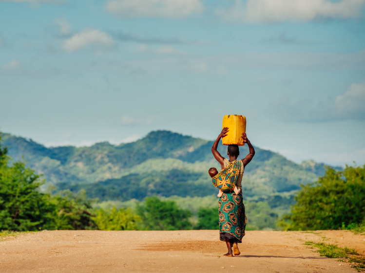 Woman carrying water - a need that will be addressed through the Solar Irrigation Project